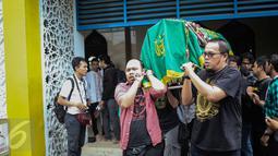 Para kerabat menggotong keranda alm Guntoro di Lenteng Agung, Jakarta, Kamis (16/2). Diduga terkena serangan jantung , Guntoro, wartawan foto, Koran Jakarta meninggal dunia saat meliput banjir di daerah Pejaten Timur. (Liputan6.com/Faizal Fanani)