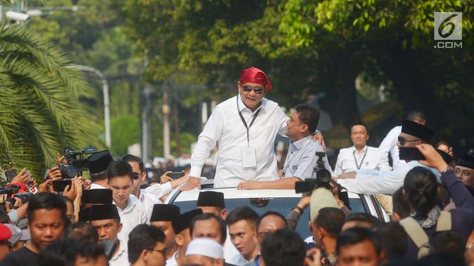 Ketua umum Partai Gerindra Prabowo Subianto mengenakan bandana merah menyapa para pendukungnya usai mendaftarkan bakal calon pasangan Presiden dan wakil presiden di Komisi Pemilihan Umum (KPU), Jakarta, Jumat (10/8).(Merdeka.com/Imam Buhori)