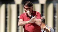 Presiden Brasil Jair Bolsonaro batuk saat berbicara dalam protes karantina dan jarak sosial untuk memerangi wabah virus corona COVID-19 di Brasilia, Brasil, 19 April 2020. Bolsonaro sempat dinyatakan negatif COVID-19 setelah beberapa ajudannya positif kena virus. (Sergio LIMA/AFP)