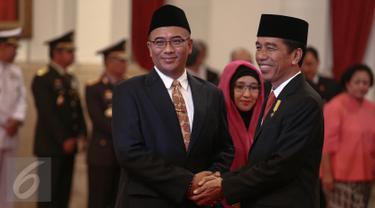 Presiden Jokowi memberi selamat kepada Hasyim Asy'ari seusai pelantikan Ketua Komisi Pemilihan Umum (KPU) di Istana Negara, Jakarta, Senin (29/8). Hasyim menggantikan posisi Husni Kamil Manik yang meninggal pada Juli lalu. (Liputan6.com/Faizal Fanani)
