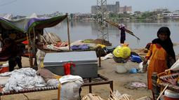 Warga yang tinggal di daerah dataran rendah berlindung di tepi sungai, di Hyderabad, Pakistan, Selasa (30/7/2019). Departemen Meteorologi Pakistan mengatakan bahwa hujan memasuki provinsi Sindh dari Rajasthan India dan memperkirakan hujan akan turun tiga hari lagi. (AP Photo/Fareed Khan)