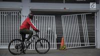 Pesepeda mengamati kerusakan pintu masuk zona 9 Stadion Utama Gelora Bung Karno pada Final Piala Presiden 2018, Jakarta, Minggu (18/2). Kerusakan tersebut disebabkan suporter salah satu tim sepakbola yang memaksa masuk. (Liputan6.com/Faizal Fanani)