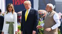 PM India, Narendra Modi berbincang dengan Presiden AS Donald Trump dan Melania Trump saat menyambut kedatangan mereka di Bandara Internasional Sardar Vallabhbhai Patel di Ahmedabad, Senin (24/2/2020). Ini merupakan kunjungan balasan Trump setelah Modi berkunjung ke AS pada 2019. (MANDEL NGAN/AFP)