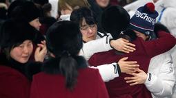 Pemain tim hoki wanita Korea Utara memeluk rekannya asal Korea Selatan saat akan kembali ke negaranya usai mengikuti Olimpiade Pyeongchang di Olympic Village, Gangneung, Korea Selatan, Senin (26/2). (Yun Dong-jin/Yonhap via AP)