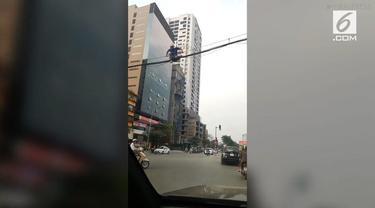 Lelah menunggu waktu menyebrang karena jalanan yang padat, membuat seorang pejalan kaki di Hanoi, Vietnam, nekat melintasi kabel listrik.