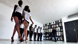 Dua orang wanita berjalan saat mengikuti pelatihan catwalk di agen model Fatim Sidime di Abidjan, Pantai Gading (20/12). Calon model ini ikut pelatihan diberi materi oleh koreografer Franck Akesse. (AFP Photo/Sia Kambou)