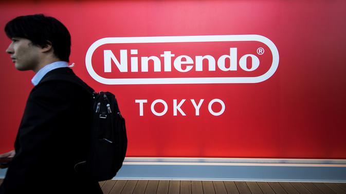 Seorang pria berjalan melewati logo Nintendo Co. Jepang yang dipajang di toko baru Nintendo di Tokyo, 19 November 2019. Nintendo akan meresmikan toko pertamanya di ibu kota Jepang tersebut pada pekan ini. (Behrouz MEHRI/AFP)