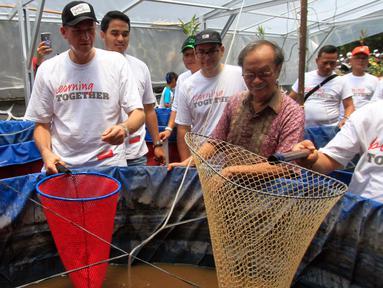 Presiden Direktur PT Prudential Indonesia Jens Reisch (kiri) meninjau kolam bioflok di Asrama Dinas Lingkungan Hidup Jakarta, Jakarta, Sabtu (28/10). Prudential Indonesa memberikan kontribusi pemberdayaan budidaya ikan air tawar. (Liputan6.com)