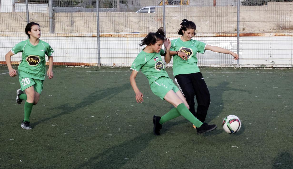 Dua pesepak bola putri klub Beit Umar Palestina berebut bola saat mengikuti sesi latihan di sebuah lapangan di Kota Hebron. (AFP/Hazem Bader)