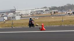Pekerja melintasi sisi landasan pacu atau runway Bandara Internasional Yogyakarta, Kulon Progo, DI Yogyakarta, Rabu (24/4). Landasan pacu Bandara Internasional Yogyakarta memiliki panjang 3.250 meter dengan lebar 45 meter. (Liputan6.com/Helmi Fithriansyah)
