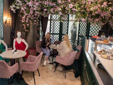 Para pelanggan menyantap makanan di samping maneken yang mengenakan busana kreasi desainer lokal di sebuah kafe di Kota Tua Vilnius, Lithuania, Kamis (21/5/2020). Sejumlah restoran dan kafe di Lithuania memamerkan koleksi busana karya desainer lokal yang terdampak COVID-19. (Xinhua/Alfredas Pliadis)