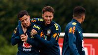 Pemain timnas Brasil Neymar menjaili rekan setimnya Philippe Coutinho saat sesi latihan di London, Inggris (29/5). Neymar dan rekan-rekannya melakukan latihan jelang pertandingan persahabatan melawan Kroasia. (AP / Kirsty Wigglesworth)