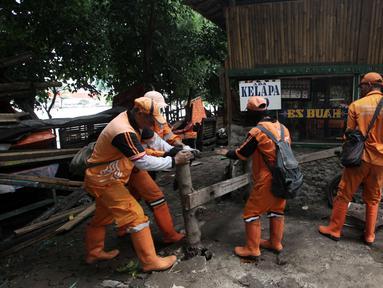 Petugas Penanganan Sarana dan Prasarana Umum (PPSU) DKI Jakarta membongkar lapak pedagang di kawasan Danau Sunter, Jakarta Utara, Jumat (19/1). Penataan ini dilakukan untuk mendukung Festival Danau Sunter pada Februari 2018. (Liputan6.com/Arya Manggala)