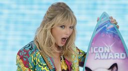 Ekspresi Taylor Swift saat menerima penghargaan Icon Award selama FOX's Teen Choice Awards 2019 di Hermosa Beach, California (11/8/2019). Penyanyi 29 tahun ini tampil cantik mengenakan busana keluaran Versace.  (Rich Fury/Getty Images/AFP)