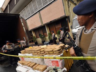 Sejumlah petugas kepolisian mengamankan barang bukti narkoba jenis ganja dan mobil tronton box sebesar dua ton hasil penangkapan ganja Aceh di Polres Jakarta Barat, Jumat (13/2/2015). (Liputan6.com/Faizal Fanani)