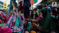 Pengunjung membeli busana muslim yang dijual di Pasar Tanah Abang, Jakarta Pusat, Minggu (2/5/2021). Pusat Grosir Pasar Tanah Abang ramai didatangi pengunjung yang berbelanja menjelang Lebaran dengan berdesak-desakan tanpa jaga jarak. (Liputan6.com/Johan Tallo)