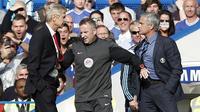 Seorang ofisial pertandingan (tengah) harus memisahkan manajer Arsenal Arsene Wenger (kiri) dan Jose Mourinho (kanan) yang terlibat friksi pada 2014. (AFP/Adrian Dennis)