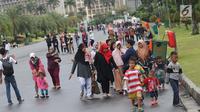 Warga bersama anak-anak berjalan-jalan di kawasan Monumen Nasional, Jakarta, Jumat (19/4). Libur panjang perayaan Paskah 2019 dimanfaatkan warga untuk berwisata di kawasan Monumen Nasional. (Liputan6.com/Helmi Fithriansyah)