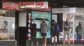 Para pria antre untuk memotong rambut di luar barber shop di Melbourne, Australia, Senin (19/10/2020). Warga Kota Melbourne, pada Senin (19/10), akhirnya bisa bernafas lega saat sejumlah pembatasan dilonggarkan setelah lockdown tahap keempat yang ketat selama sekitar 100 hari. (William WEST/AFP)