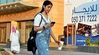 Manahel Otaibi, 25, memeriksa teleponnya saat dia berjalan dengan pakaian ala Barat di Tahlia Street, Riyadh, Arab Saudi, pada 2 September 2019. (Fayez Nureldine / AFP)