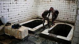 Pengunjung melumuri tubuhnya menggunakan lumpur dari sumber belerang guna menyehatkan kulit mereka di Hamam Alli, Mosul, Irak, (27/4). (AP Photo/Bram Janssen)