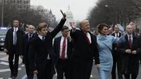 Barron Trump bersama Donald Trump dan Melania melambaikan tangannya ke arah pengunjung saat parade pelantikan di Washington (EVAN VUCCI / POOL / AFP)
