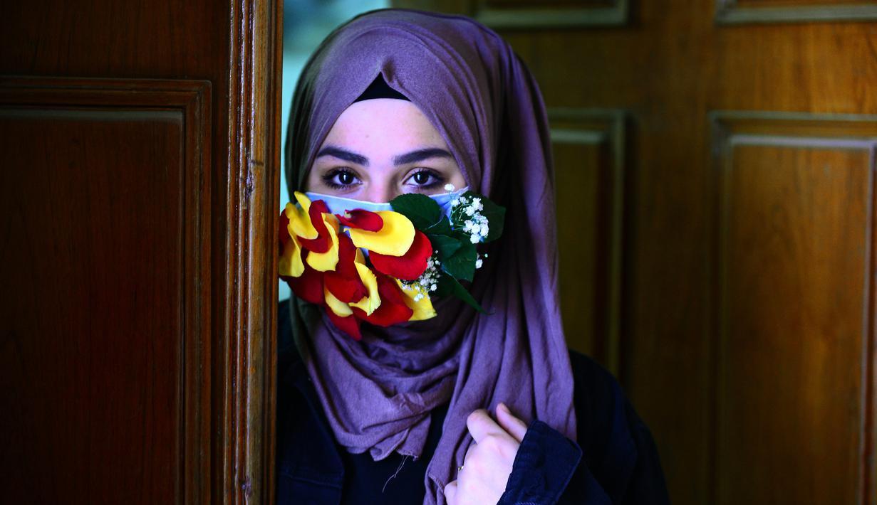Seorang perempuan mengenakan topeng yang dihiasi kelopak bunga di tengah virus corona (Covid-19) di pusat kota suci Najaf, Irak pada 21 Maret 2020. Masker dijadikan masyarakat pilihan untuk mencegah penyebaran pandemi virus corona yang terus meningkat di seluruh dunia. (Haidar HAMDANI/AFP)