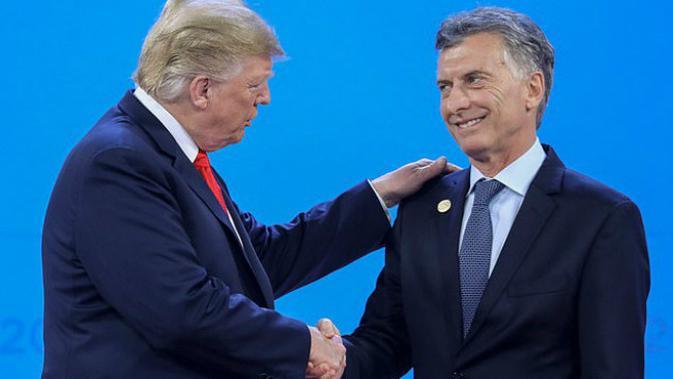 Presiden AS Donald Trump (kiri) menjabat tangan Presiden Argentina Mauricio Macri di panggung foto bersama KTT G20 (1 12) (AFP PHOTO)