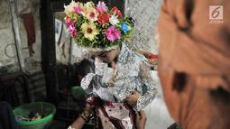 Gadis dirias oleh keluarga sebelum mengikuti Upacara Adat Ngarot di Desa Lelea, Kabupaten Indramayu, Jawa Barat, Rabu (19/12). Para gadis didandani mengenakan setelan kebaya dan kain batik dipadu dengan selendang. (Merdeka.com/Iqbal Nugroho)