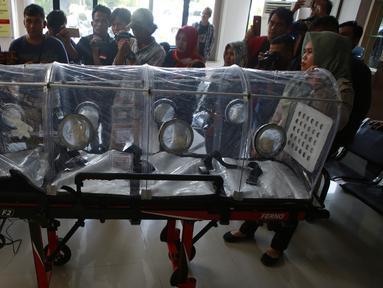 Petugas kesehatan Pelabuhan Kelas II Panjang menunjukkan tandu pelindung (isolation camber) di Lampung, Selasa (28/1/2020). Isolation camber ini menyerupai sebuah tandu yang dilengkapi dengan penutup sebagai ruang isolasi sementara untuk melindungi pasien terjangkit virus corona. (AFP/Perdiansyah)