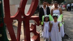 Pasangan bersama anak-anak mereka berpose selama pernikahan massal sebagai bagian dari perayaan Hari Valentine di Manila, Filipina (14/2). Sekitar 200 pasangan dilaporkan ikut serta dalam acara tersebut. (AFP Photo/Ted Aljibe)