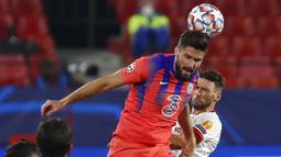 Striker Chelsea, Olivier Giroud, menyundul bola saat melawan Sevilla pada laga Liga Champions di Stadion Ramon Sanchez Pijuan, Kamis (3/12/2020). Chelsea Menang dengan skor 4-0. (AP/Angel Fernandez)