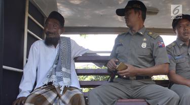 Petugas Satpol PP Kota Bogor mengamankan pengemis yang sempat viral di kawasan perempatan Yasmin, Bogor, Jawa Barat, Rabu (20/3). Kepada awak media, pengemis tersebut membantah memiliki mobil. (merdeka.com/Arie Basuki)