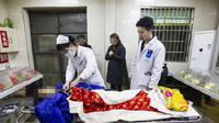 (Foto: The Paper) Tim medis yang datang memeriksa keadaan Huang.