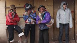 Sejumlah pria Andean dan seorang wisatawan meneduh saat hujan di Gunung Pelangi di Pitumarca, Peru (5/4). Rainbow Mountain terdiri dari hamparan pasir berwarna-warni seperti pelangi. (AP Photo/Martin Mejia)