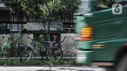 Kendaraan melintas di dekat warga yang sedang memancing di Kali Ancol, Jakarta Utara, Kamis (11/3/2021). Ikan yang biasa didapat warga antara lain bawal dan mujair. (merdeka.com/Iqbal S. Nugroho)
