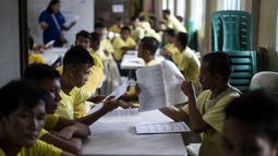 Narapidana mengerjakan soal Ujian Akreditasi Nasional dan Pemeriksaan Kesetaraan di Penjara Manila City, Filipina, Minggu (19/11). Sekitar 900 narapidana mengikuti ujian untuk menjadi modal pendidikan mereka jika bebas dari penjara. (NOEL CELIS/AFP)