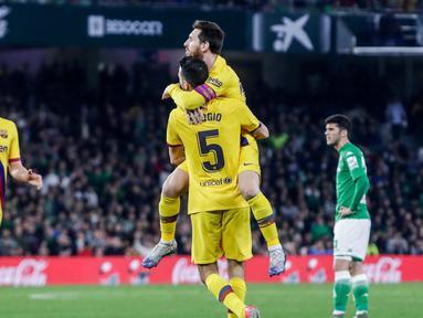 Gelandang Barcelona, Sergio Busquets disambut rekan timnya Lionel Messi usai mencetak gol ke gawang Real Betis pada lanjutan Liga Spanyol pekan ke-23 di Benito Villamarin, Minggu (9/2/2020). Diwarnai dua kartu merah, Barcelona mememangkan duel menegangkan lawan Real Betis 3-2. (AP/Miguel Morenatti)