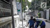Petugas dari Dinas Sumber Daya Air Pemprov DKI sedang membersihkan saluran air di Jalan Lebak Bulus II, Jakarta, Selasa (16/4). Pembersihan dilakukan lantaran lokasi tersebut akan dijadikan TPS 28 dimana Gubernur Anies Baswedan menggunakan hak suaranya dalam Pemilu 2019. (Liputan6.com/Faizal Fanani)