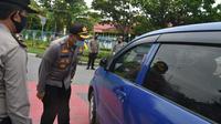 Polisi mengecek penumpang di Pekanbaru karena pemberlakuan pembatasan sosial. (Liputan6.com/M Syukur)