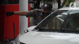 Seorang satpam berbincang dengan pengendara mobil di salah satu perkantoran kawasan Jakarta, Selasa (16/2/2021). Seragam baru berwarna cokelat mirip seragam polisi tersebut untuk memuliakan Satpam dan menjadikan unsur pengamanan menjadi bagian penting dalam suatu aktivitas. (merdeka.com/Imam Buhori)