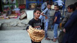 Seorang anak menerima roti gratis dari kota selama lockdown untuk mencegah penyebaran virus corona, pada bulan suci Ramadan di Kabul, Afghanistan (4/5/2020). Muslim di seluruh dunia sedang menjalankan Ramadan, ketika mereka menahan diri dari makan, minum dari subuh hingga senja. (AP/Rahmat Gul)