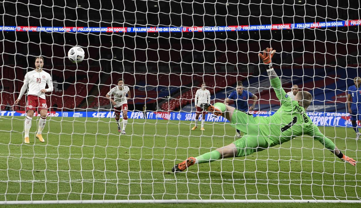 Pemain Denmark Christian Eriksen (kiri) mencetak gol ke gawang Inggris dari titik penalti pada pertandingan UEFA Nations League di Stadion Wembley, London, Inggris, Rabu (14/10/2020). Denmark menang 1-0. (Daniel Leal-Olivas/Pool via AP)