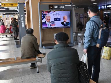 Orang-orang menonton program berita televisi tentang pemilihan presiden (pilpres) AS yang menampilkan gambar Presiden Donald Trump (kiri) dan calon presiden dari Partai Demokrat Joe Biden (kanan), di sebuah stasiun kereta api di Seoul, Korea Selatan pada Rabu (4/11/2020). (Photo by Jung Yeon-je / AF