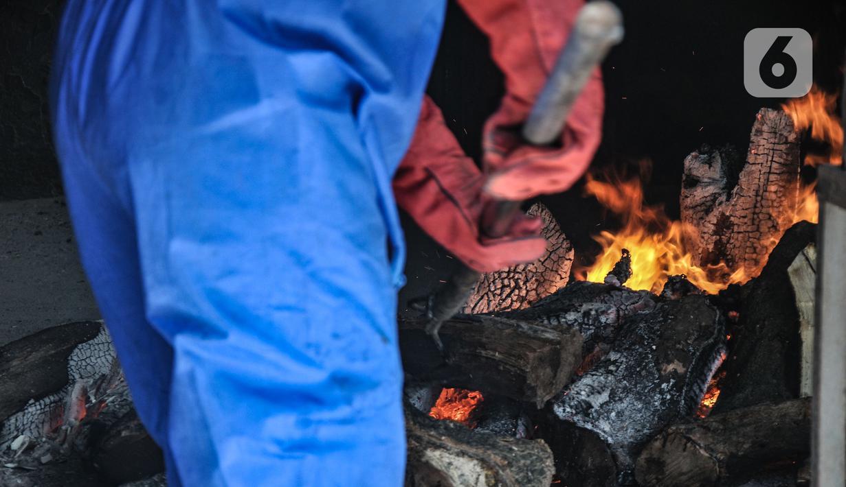 Petugas mengenakan APD saat proses kremasi jenazah pasien Covid-19 di Krematorium Cilincing, Jakarta Utara, Minggu (25/7/2021). Layanan kremasi jenazah pasien Covid-19 di Krematorium Cilincing terus bergeliat sejak dibuka pada 19 Juli 2021. (merdeka.com/Iqbal S Nugroho)