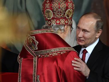 Presiden Rusia, Vladimir Putin memeluk kepala Gereja Ortodoks Rusia usai menjalani prosesi Paskah Ortodoks di Gereja Katedral Kristus Juru Selamat di Moskow, Rusia, (16/4). (AFP Photo / Vasily Maximov)