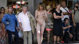"""Seorang wanita tanpa busana tampak berdiri di tempat umum saat menggelar aksi teatrikal dalam Festival """"Body and Freedom"""" di Kota Biel, Swiss, Jumat (21/8/2015). Festival ini berlangsung dari 21-22 Agustus. (AFP PHOTO/Fabrice Coffrini)"""