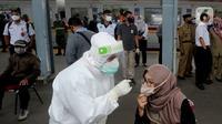 Penumpang KRL Commuter Line diperiksa suhu tubuh saat tes swab di Stasiun Bojonggeder, Jawa Barat, Senin (11/05/2020).  Tes swab dan rapid dilakaukan sebagai salah satu metode untuk mendeteksi dan mencegah penyebaran Covid-19 di moda transportasi KRL Commuter Line. (merdeka.com/Arie Basuki)