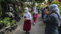 Guru menyapa para siswa sebelum mengikuti pembelajaran tatap muka (PTM) di sebuah sekolah di Surabaya, Jawa Timur, Senin (6/9/2021). Pemerintah kembali membuka sekolah di tengah pandemi COVID-19. (JUNI KRISWANTO/AFP)