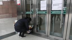 Warga menaruh bunga untuk mendiang dokter mata Li Wenliang di Cabang Houhu Rumah Sakit Pusat Wuhan di Wuhan di provinsi Hubei, China, Jumat, (7/2/2020). Li Wenliang meninggal karena virus corona di Wuhan pada pukul 02.58 Jumat dini hari waktu setempat. (AFP/STR)